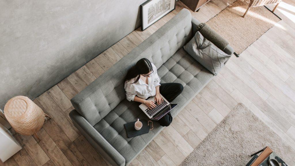 Eine Frau auf der Couch vor einem Laptop | photocademy